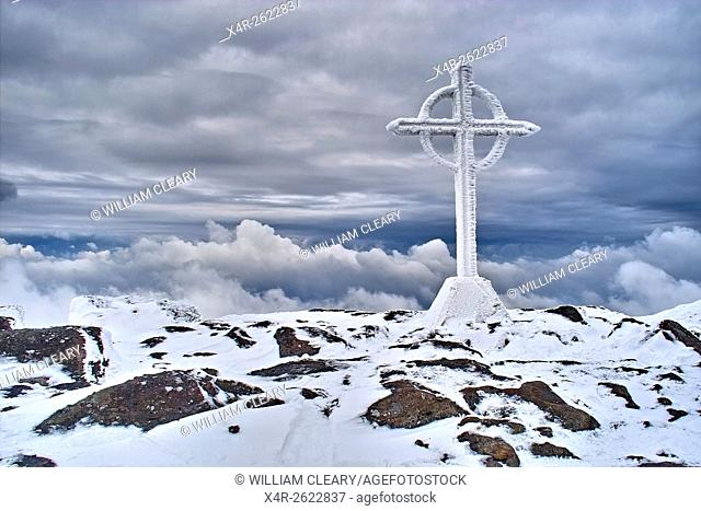 The summit cross on the snow covered summit of Galtymore, Galtee Mountains, County Tipperary, Ireland