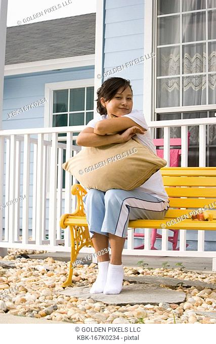 Young Asian woman sitting on a bench hugging a pillow in front of house
