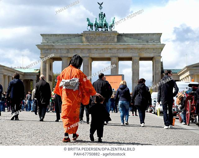 A Japanese woman wearing a kimono stands with her son in front of the Brandenburg Gate in Berlin, Germany, 25 April 2016
