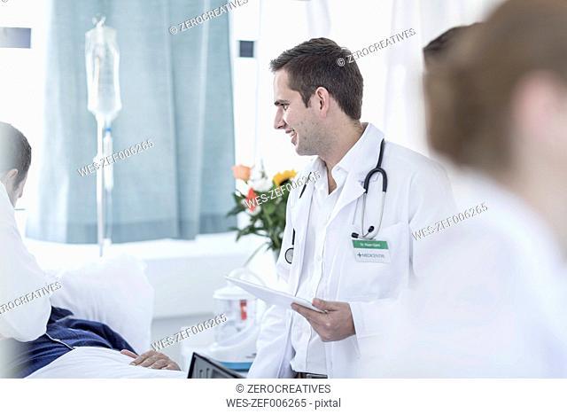Doctors examining patient in a hospital room