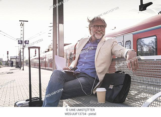 Smiling mature businessman sitting at train station with cell phone, earbuds and notebook