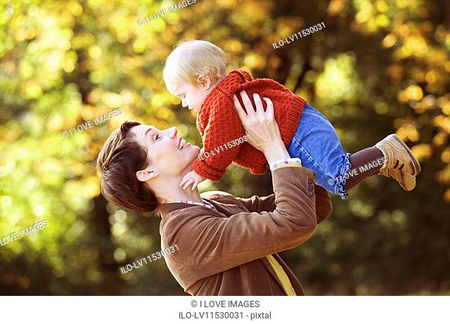 A young mother lifting her baby in the air playfully