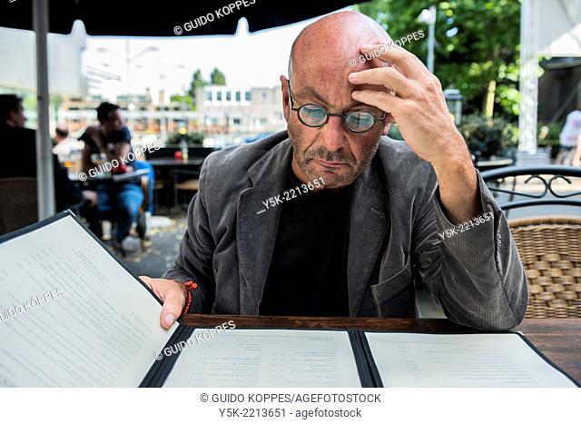 Tilburg, Netherlands. Bald, be glassed and middle-aged man, studying on a restaurant's menu, before ordering diner