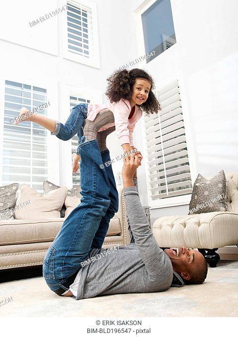 Father lifting daughter on his feet