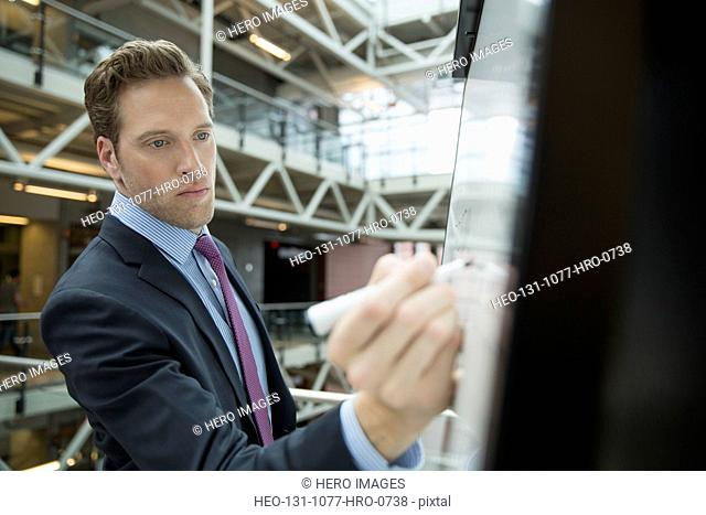 Businessman writing on whiteboard in office atrium