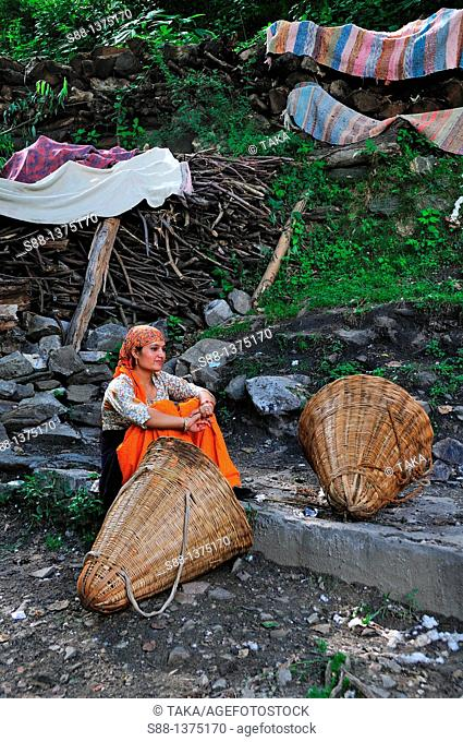 Woman having rest at public washing place where they get water by the big tree