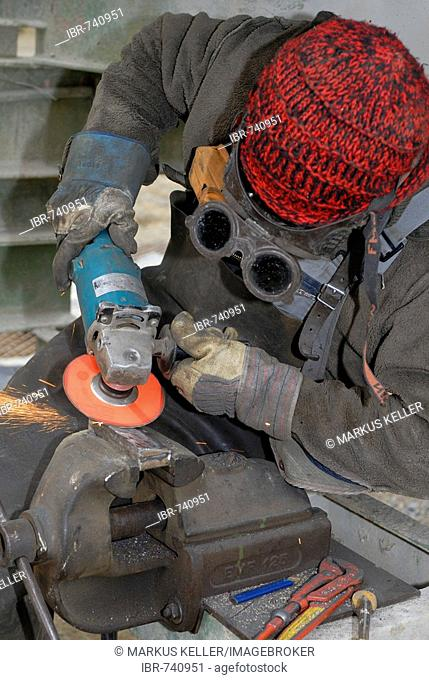 Man working metal with angle grinder