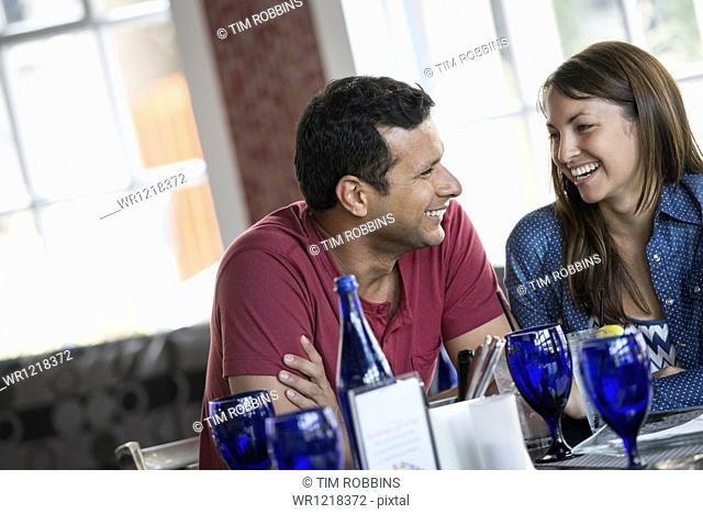 A cafe interior. A couple seated at a table