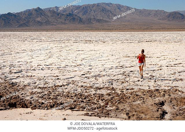Woman visiting Salt Pan at Amboy Crater National Natural Landmark, Mojave Desert, California, USA