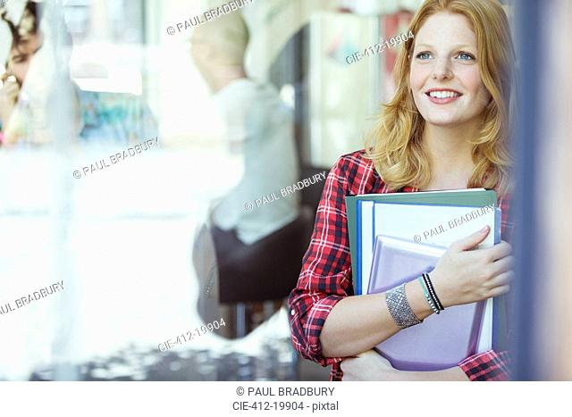 Woman carrying binders outdoors
