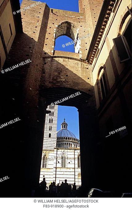Italy, Tuscany, Siena, Duomo cathedral, dome and campanile, people, framed by part of a never-completed larger cathedral