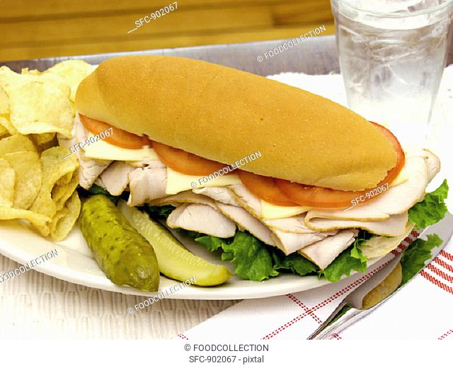 A Turkey Sub with Potato Chips and Pickles