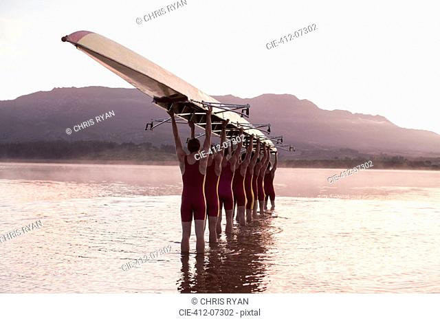 Rowing team carrying row boat overhead in still lake