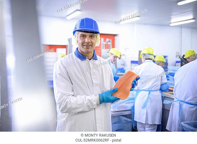 Worker holding fish filet in factory