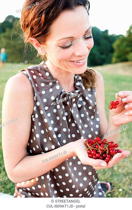 Mature woman eating redcurrants in park