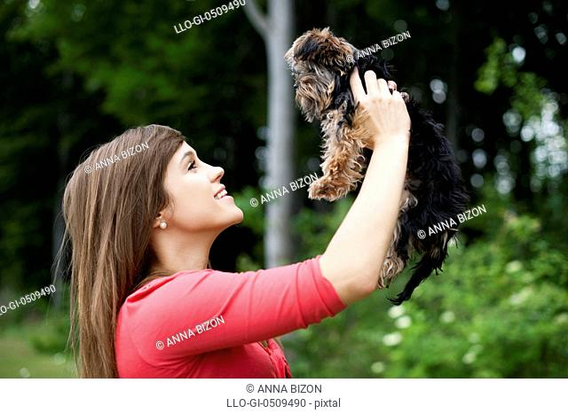 Smiling woman holding cute puppy Debica, Poland