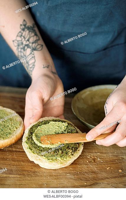 Woman preparing vegan burger, spreading avocado cream on fritter