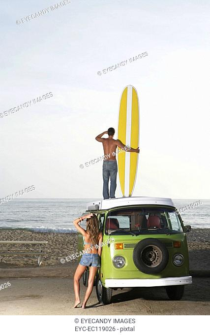Man standing on roof of van with surfboard