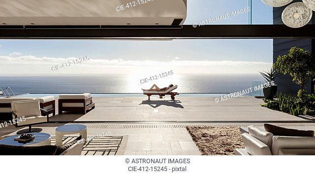 Woman sunbathing on lounge chair at poolside overlooking ocean