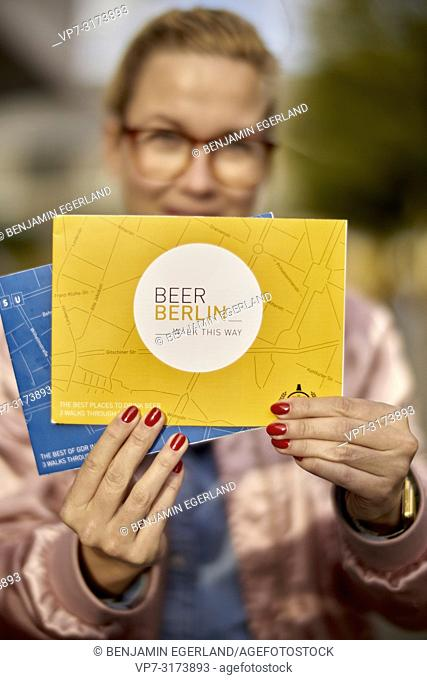 Woman with city tour guide maps in Berlin, Germany