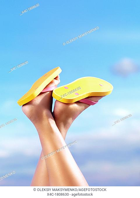 Close up of woman legs wearing bright yellow flip flops under blue sky background