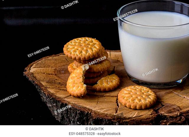 fresh healthy milk in cup and stack of cookies on black background