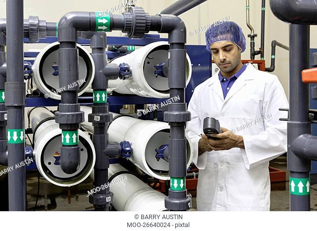 Worker holding an equipment in bottling plant
