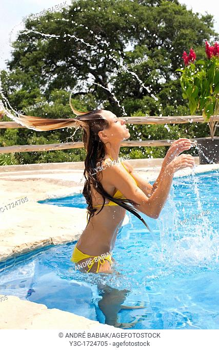 Woman throwing her hair in swimming pool