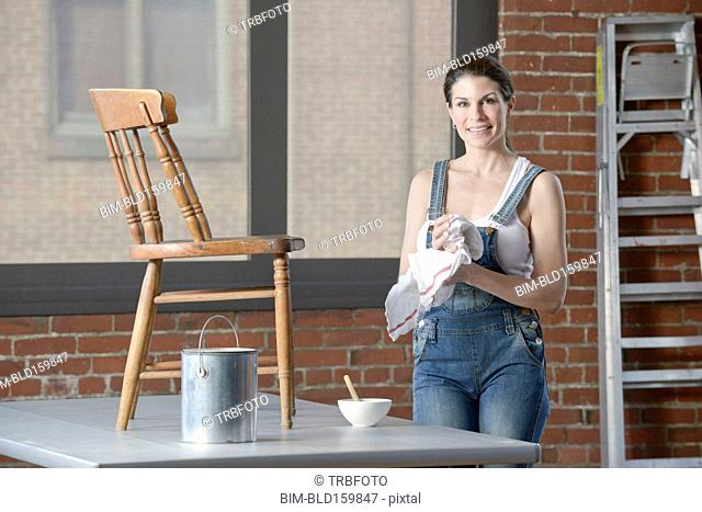 Mixed race woman painting chair in loft