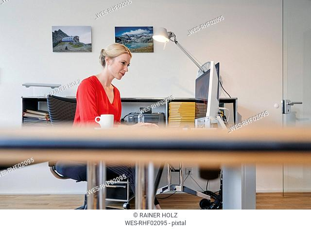 Young woman working on computer at desk in office