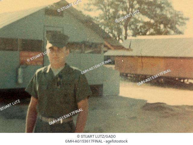 American soldier standing near military barracks in Vietnam during the Vietnam War, 1968. ()
