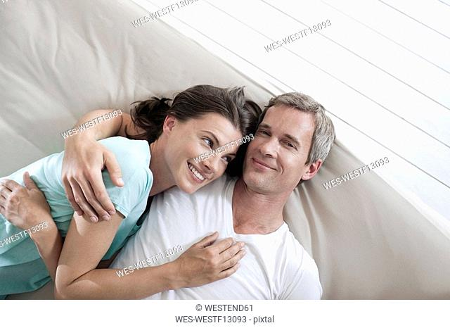 Germany, Hamburg, Couple lying in bed, elevated view