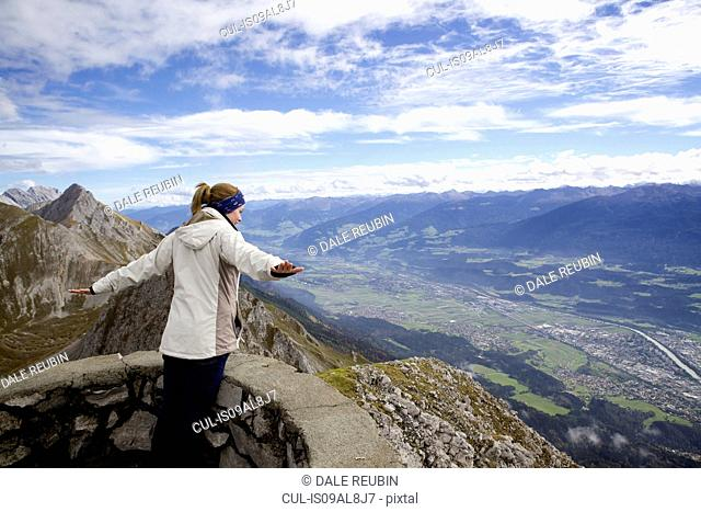Young woman with arms open on top of mountain, Innsbruck Tyrol, Austria
