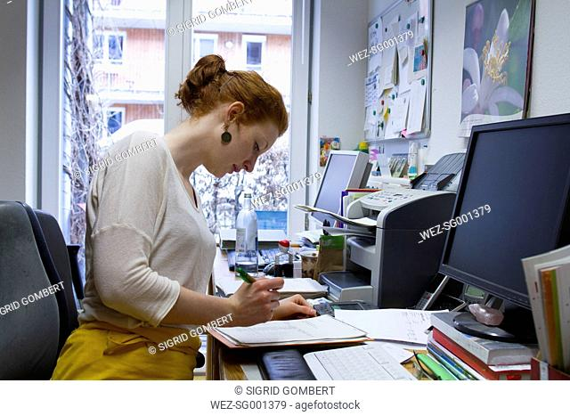 Young woman checking form in an office