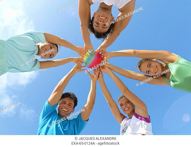 Low angle view of people in a circle holding a ball