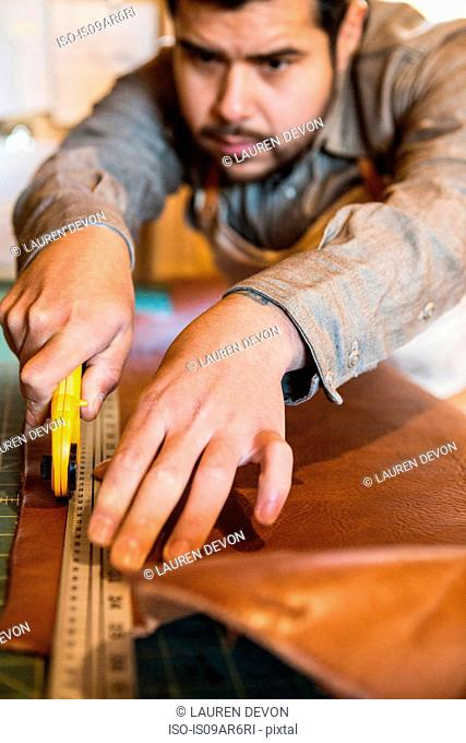 Leather craftsman using rotary cutter on workshop bench
