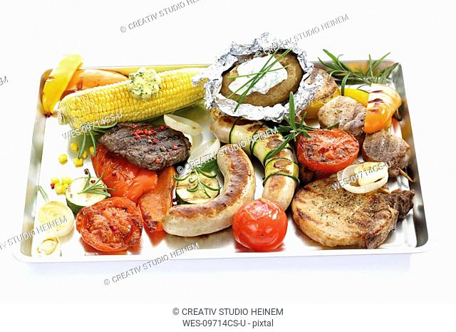 Grilled meat, sausage and vegetables on tray