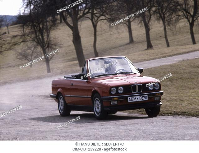 Car, 3er BMW convertible, model year 1985-1993, red, old car, 1980s, eighties, open top , driving, diagonal front, front view, road, country road