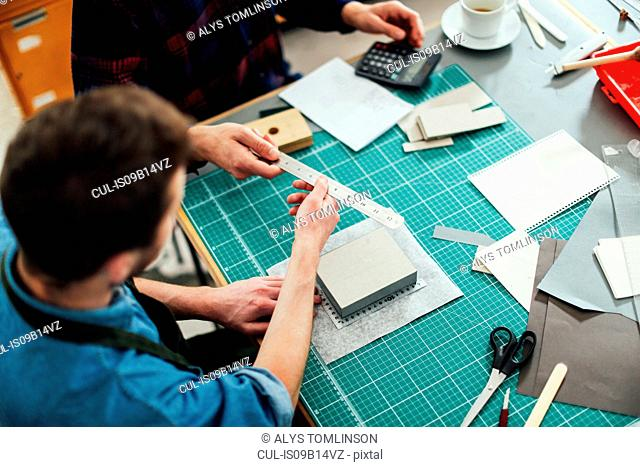 Young craftsman passing metal ruler to friend in print studio, elevated view