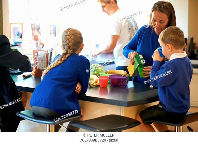 Mother pouring juice for her school children in kitchen