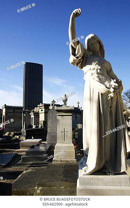 A tomb statue in Cimetiere du Montparnasse with the high-rise Tour Montparnasse in the background. Paris. France