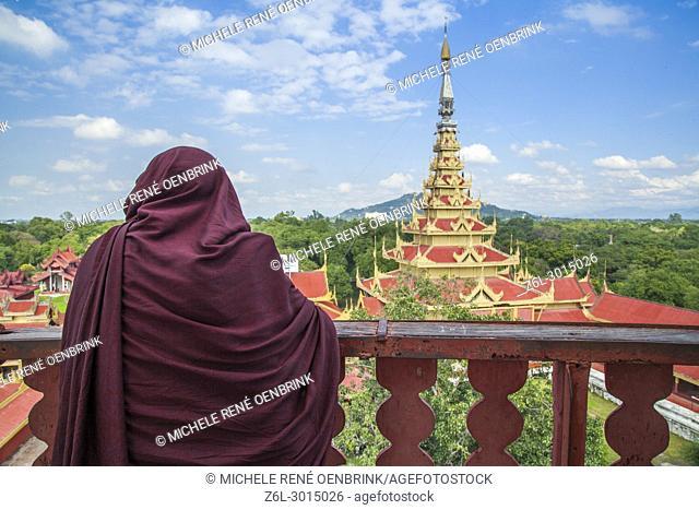 Monk overlooking Mandalay Royal Palace in Mandalay Myanmar