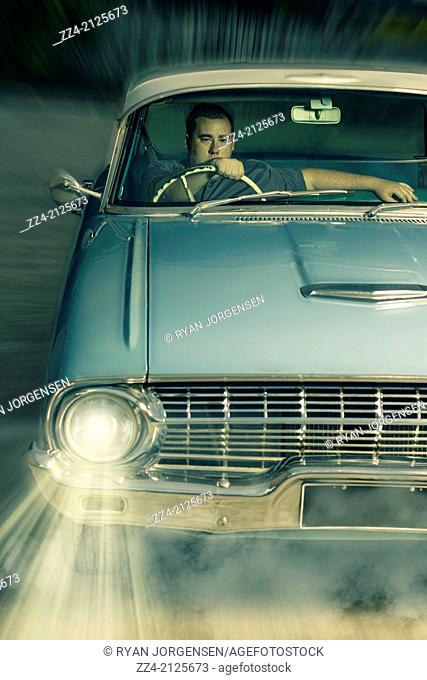 1950s classic portrait of a man driving old chrome vehicle through diner drive-thru. 1950s American car culture