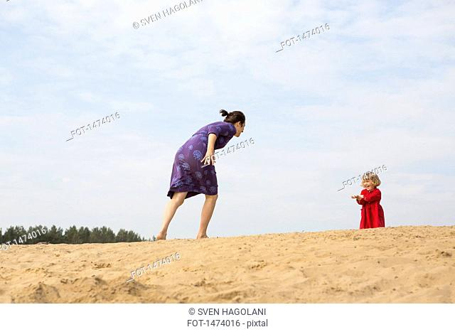 Mother and daughter playing on sand against sky