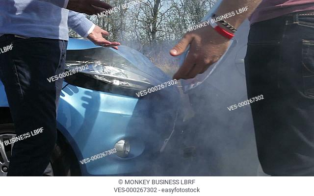 Two drivers argue about blame for accident by the side of damaged and smoking vehicles - camera pans from feet to faces.Shot on Canon 5d Mk2 with a frame rate...