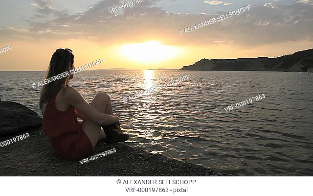 WS, A woman sitting by the sea at sunset