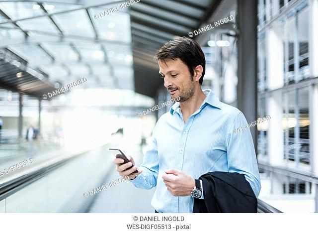 Businessman on a moving walkway, using smartphone