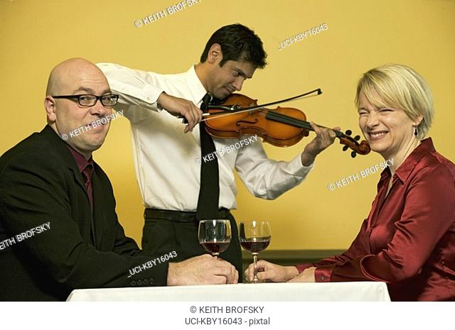 Waiter playing romantic music for two friends