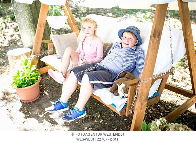 Sister and brother sitting in canopy swing