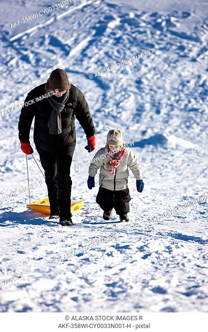 Mother and daughter walking up the sled hill after sleding down it during Winter, Anchorage, Southcentral Alaska